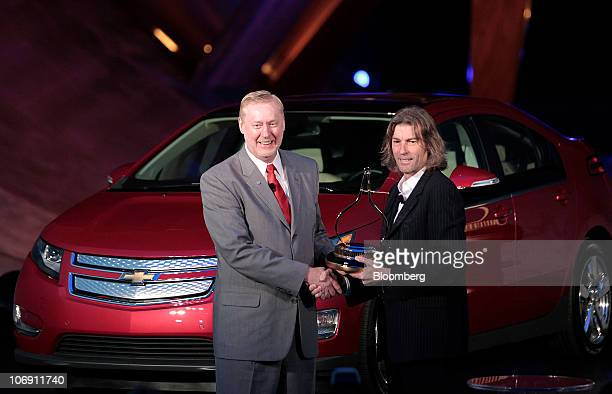 Tom Stephens vice chairman of global product operations for General Motors Co left shakes hands with Angus MacKenzie editorinchief of Motor Trend...