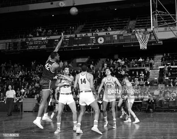 Tom Stith of the St Bonaventure Bonnies fires a lefthanded jump shot over Manhattan Jaspers defenders during a consolation game of the ECAC Holiday...
