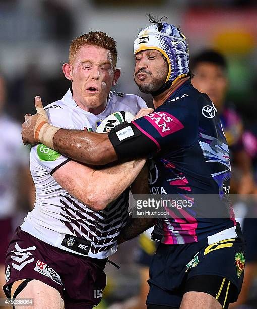 Tom Symonds of the Sea Eagles is tackled by Johnathan Thurston of the Cowboys during the round 12 NRL match between the North Queensland Cowboys and...