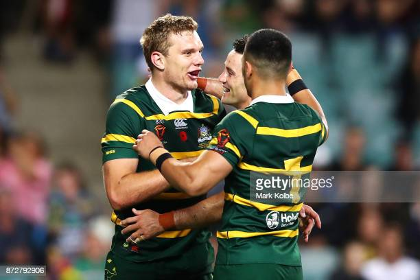 Tom Trbojevic of Australia celebrates with his team mates Cooper Cronk and Valentine Holmes of Australia after scoring a try during the 2017 Rugby...