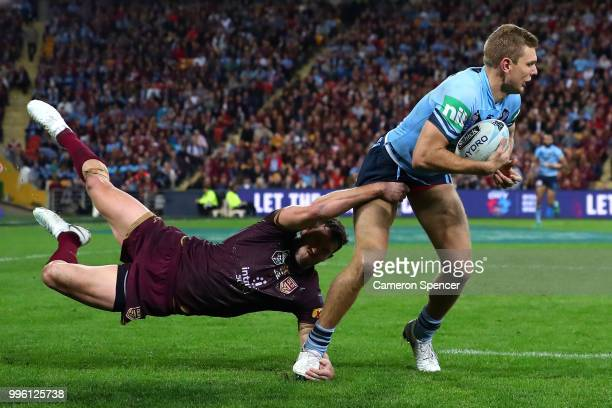 Tom Trbojevic of the Blues breaks through the tackle of Corey Oates of Queensland during game three of the State of Origin series between the...