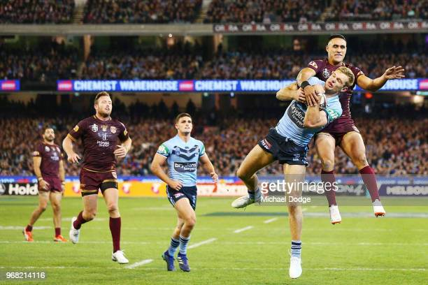 Tom Trbojevic of the Blues catches the ball against Valentine Holmes of the Maroons during game one of the State Of Origin series between the...