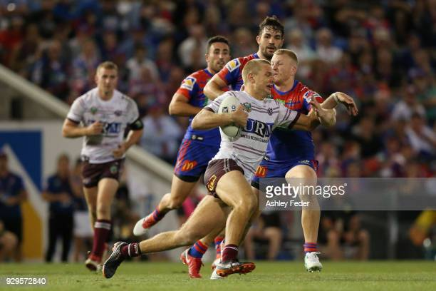 Tom Trbojevic of the Sea Eagles is tackled by the Knights defence during the round one NRL match between the Newcastle Knights and the Manly Sea...