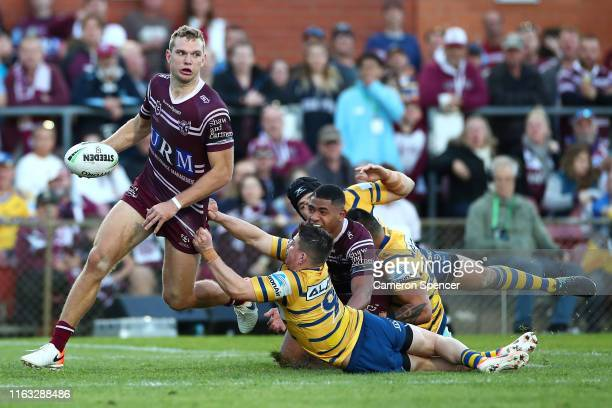 Tom Trbojevic of the Sea Eagles is tackled during the round 18 NRL match between the Manly Sea Eagles and the Parramatta Eels at Lottoland on July 21...