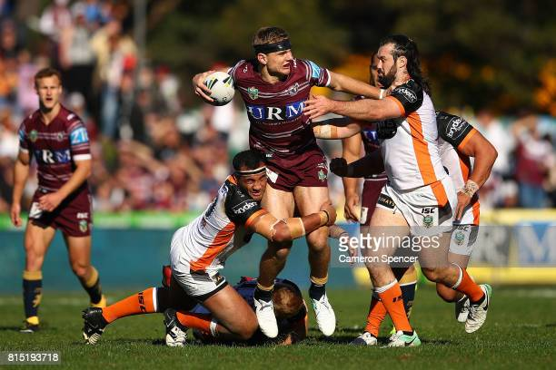 Tom Trbojevic of the Sea Eagles is tackled the round 19 NRL match between the Manly Sea Eagles and the Wests Tigers at Lottoland on July 16 2017 in...