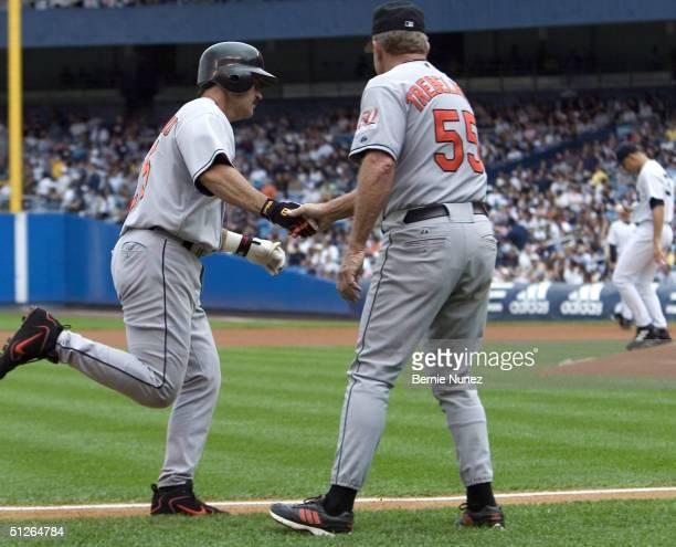 Tom Trebelhorn congratulates Rafael Palmeiro of the Baltimore Orioles after hitting a three run homerun in the first inning off pitcher Javier...
