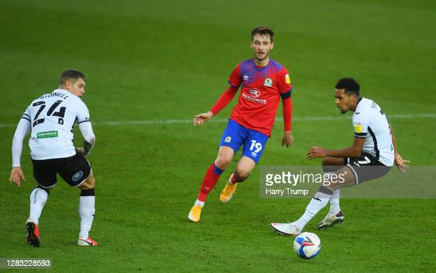 Tom Trybull of Blackburn Rovers looks to break past Korey Smith and Jake Bidwell of Swansea City during the Sky Bet Championship match between...