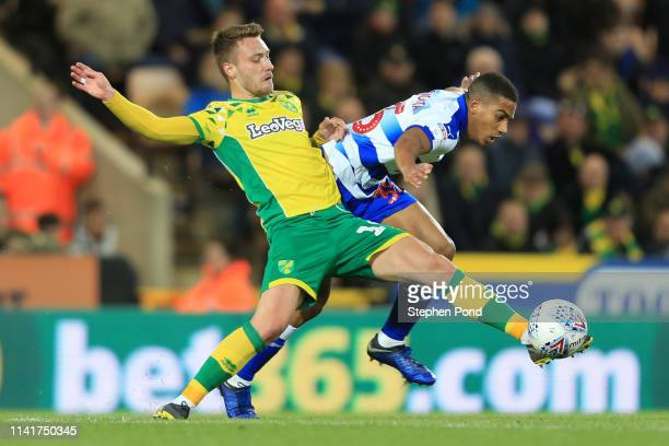 Tom Trybull of Norwich City is challenged by Andy Rinomhota of Reading during the Sky Bet Championship match between Norwich City and Reading at...