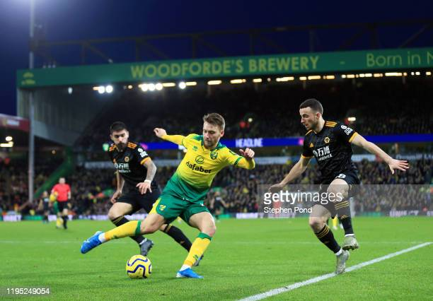 Tom Trybull of Norwich City is put under pressure by Diogo Jota of Wolverhampton Wanderers during the Premier League match between Norwich City and...