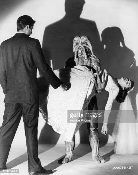 Tom Tryon stands before alien holding Gloria Talbott in a scene from the film 'I Married A Monster From Outer Space' 1958