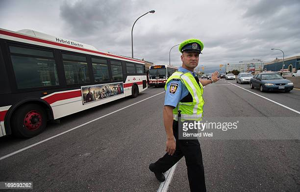 Tom Tsomis stops traffic to let a steady stream of TTC shuttle busses get underway at the Lawrence station following a shut down of the subway line A...