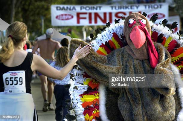 Tom Turkey aka 15–yr–old Ryland Harris of Laguna Beach gives a high five near the finish line of the 5K run The 26th Annual Ralphs Dana Point Turkey...
