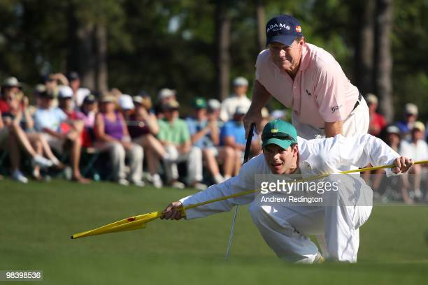 Tom Watson lines up a putt on the 18th green with his son/caddie Mike during the final round of the 2010 Masters Tournament at Augusta National Golf...