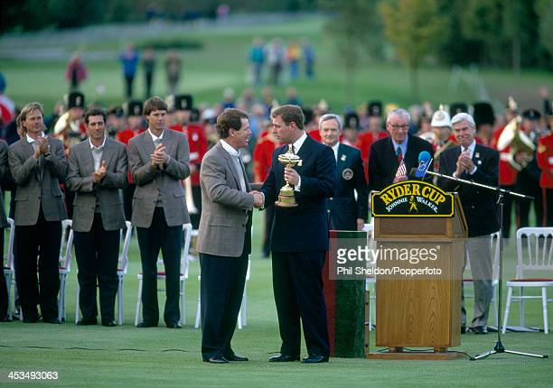 Tom Watson nonplaying captain of the United States team is presented with the trophy by HRH Prince Andrew after the United States team wins the Ryder...