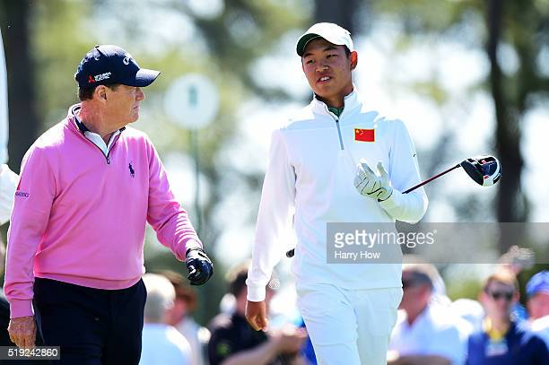 Tom Watson of the United States and Cheng Jin of China walk down the fairway during a practice round prior to the start of the 2016 Masters...
