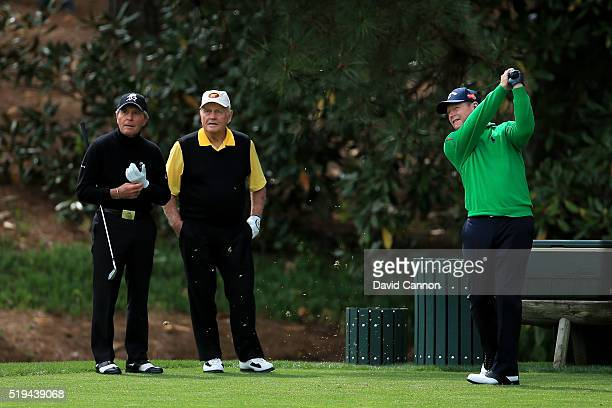 Tom Watson of the United States plays a shot as Jack Nicklaus and Gary Player look on during the Par 3 Contest prior to the start of the 2016 Masters...