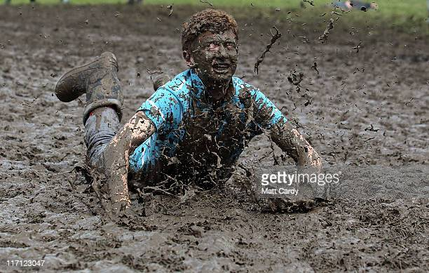 Tom Wilder, 17 from Kent, dives in the mud at the Glastonbury Festival site at Worthy Farm, Pilton on June 23, 2011 in Glastonbury, England. Music...