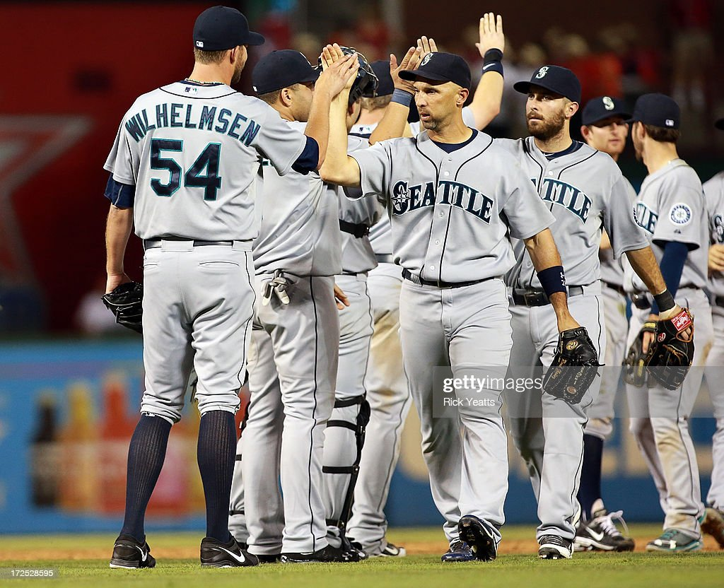 Tom Wilhelmsen #54 of the Seattle Mariners is congratulated by his teammates for closing out the game for the win against the Texas Rangers at Rangers Ballpark in Arlington on July 2, 2013 in Arlington, Texas.