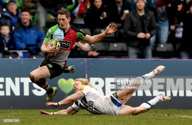Tom Williams of Harlequins skips over the challenge from Tom Biggs of Bath to score a try during the LV=Cup Semi Final match between Harlequins and...