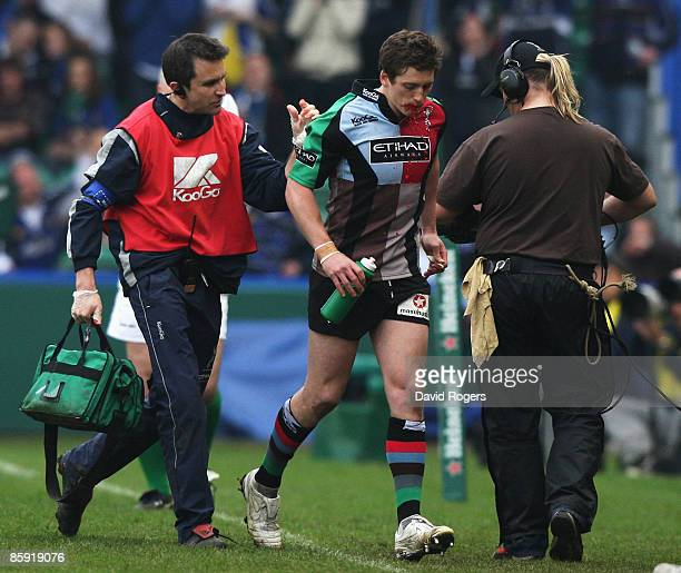 Tom Williams of Harlequins walks off with physio Steph Brennan to be replaced by team mate Nick Evans as blood pours from his mouth during the...