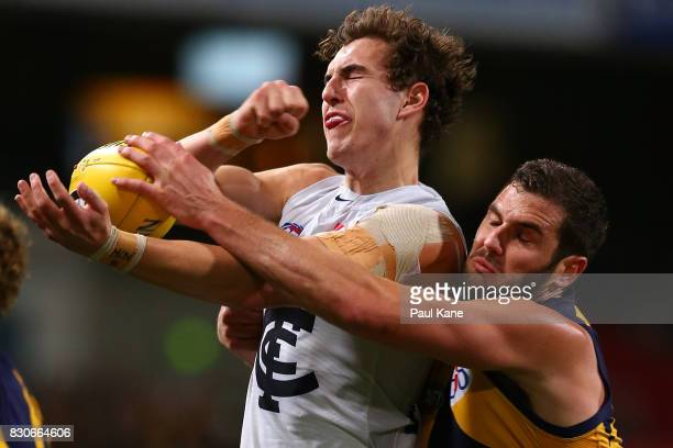 Tom Williamson of the Blues looks to handball against Jack Darling of the Eagles during the round 21 AFL match between the West Coast Eagles and the...