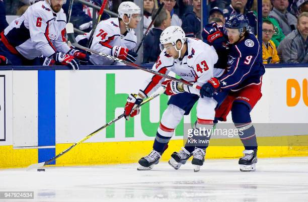Tom Wilson of the Washington Capitals and Artemi Panarin of the Columbus Blue Jackets battle for control of the puck during the first period in Game...