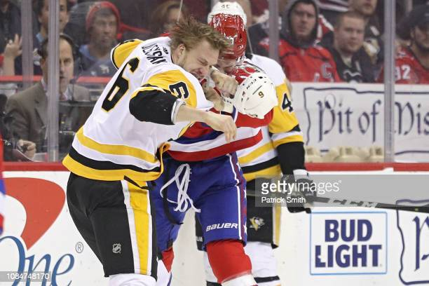 Tom Wilson of the Washington Capitals and Jamie Oleksiak of the Pittsburgh Penguins fight during the first period at Capital One Arena on December 19...