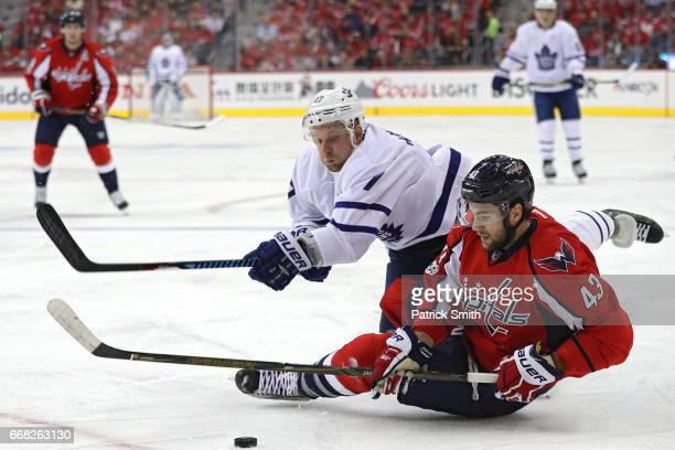 Tom Wilson of the Washington Capitals and Leo Komarov of the Toronto Maple Leafs battle for puck in the first period in Game One of the Eastern...