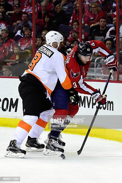 Tom Wilson of the Washington Capitals and Nicklas Grossmann of the Philadelphia Flyers battle for the puck behind the net in the third period during...