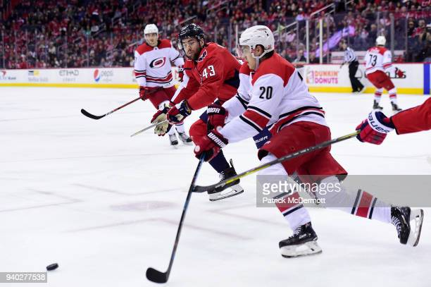 Tom Wilson of the Washington Capitals and Sebastian Aho of the Carolina Hurricanes battle for the puck in the first period at Capital One Arena on...