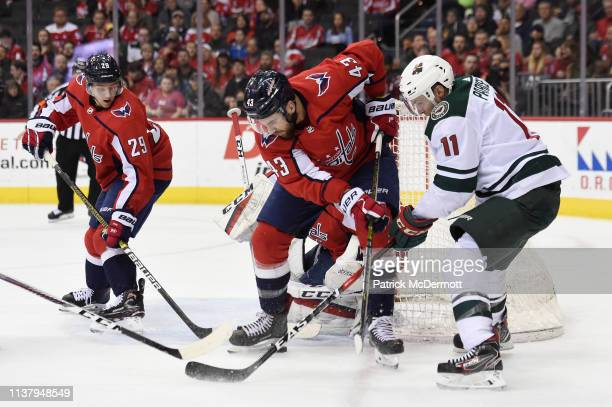 Tom Wilson of the Washington Capitals and Zach Parise of the Minnesota Wild battle for the puck in the second period at Capital One Arena on March 22...