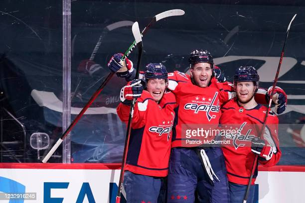 Tom Wilson of the Washington Capitals celebrates with his teammates Nick Jensen and Daniel Sprong after scoring a goal against the Boston Bruins in...