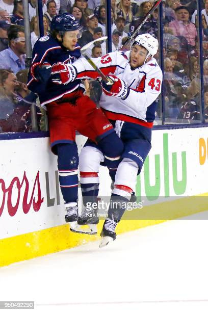 Tom Wilson of the Washington Capitals collides with Artemi Panarin of the Columbus Blue Jackets while chasing after the puck during the second period...
