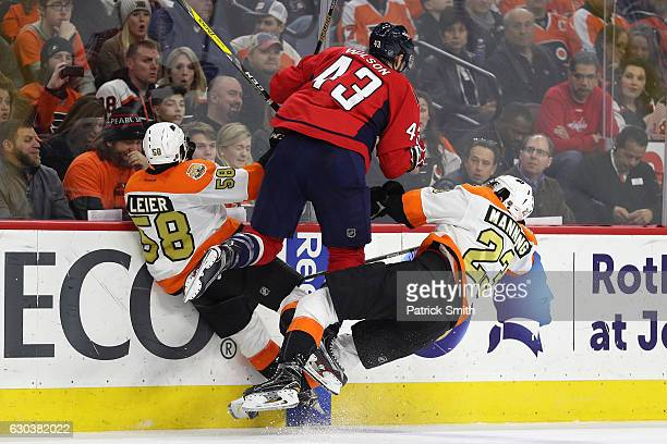 Tom Wilson of the Washington Capitals collides with Taylor Leier and Brandon Manning of the Philadelphia Flyers during the second period at Wells...