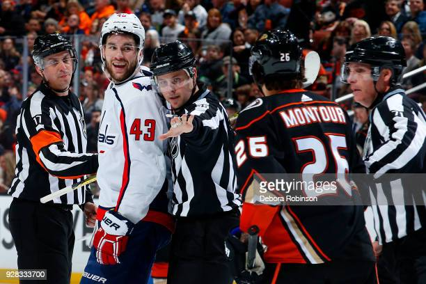 Tom Wilson of the Washington Capitals gets held back by referee Frederick L'Ecuyer and linesman Kiel Murchison as he argues with Brandon Montour of...