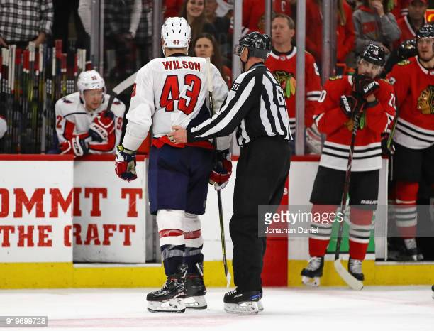 Tom Wilson of the Washington Capitals is escorted off the iice by lineman Darren Gibbs after being thrown out of a game against the Chicago...