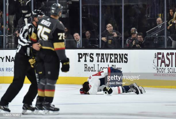 Tom Wilson of the Washington Capitals lays on the ices after a hit by Ryan Reaves of the Vegas Golden Knights during the second period of a game at...