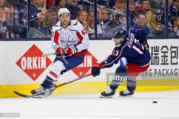 Tom Wilson of the Washington Capitals passes the puck past Cam Atkinson of the Columbus Blue Jackets in Game Three of the Eastern Conference First...
