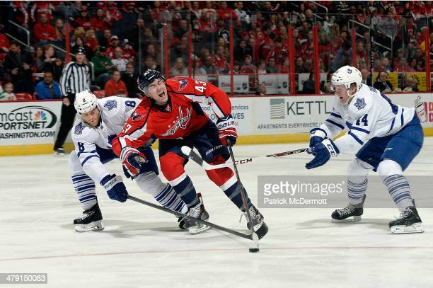 Tom Wilson of the Washington Capitals reacts as he battles for the puck against Tim Gleason and Morgan Rielly of the Toronto Maple Leafs in the...
