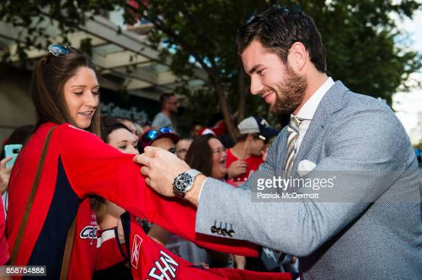 Tom Wilson of the Washington Capitals signs autographs for fans on the Rock the Red Carpet prior to the start of a game against the Montreal...