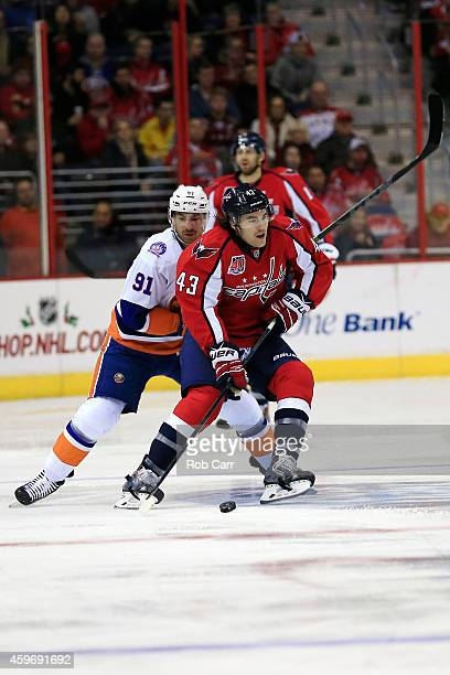 Tom Wilson of the Washington Capitals works the puck past John Tavares of the New York Islanders during the first period at Verizon Center on...