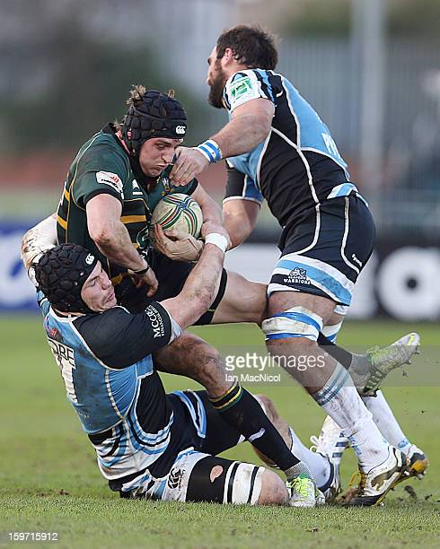 Tom Wood of Northampton is tackled by Tim Swinson and Josh Strauss of Glasgow during the Glasgow Warriors and Northampton Saints Heineken Cup Pool...
