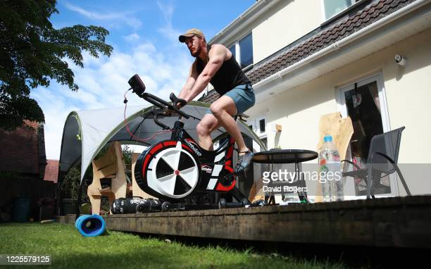 Tom Wood, the Northampton Saints and England back row forward, works out in his garden, using a Wattbike on May 18, 2020 in Northampton, United...