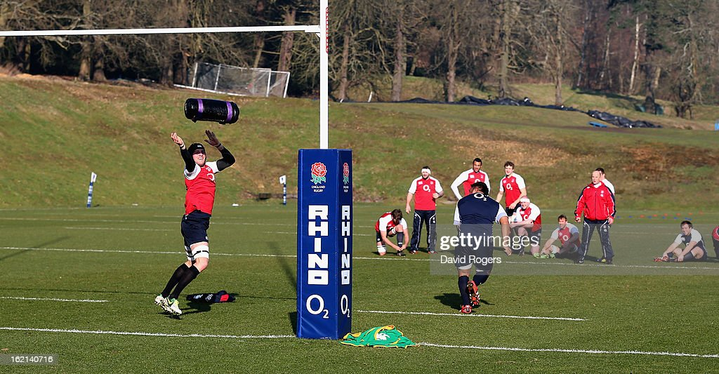 Tom Wood throws a weight over the cross bar in a team relay during the England training session held at Pennyhill Park on February 19, 2013 in Bagshot, England.
