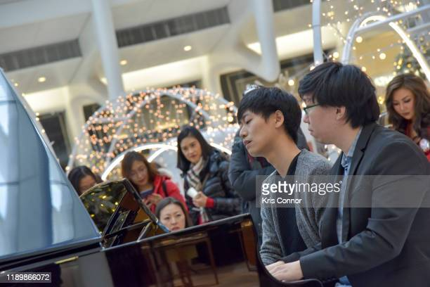 Tom Xi and John Joowon Han perform during Piano City as part of Make Music Winter at the Oculus on December 21 2019 in New York City