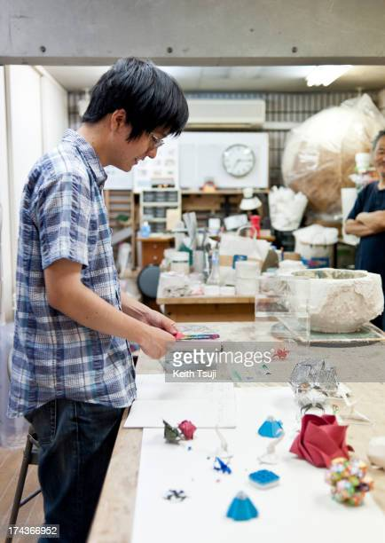 Toma Takeda demostrates how to fold his version of Kabuto on July 17 2013 in Yokohama Japan Self taught origami artist Toma Takeda discovered...