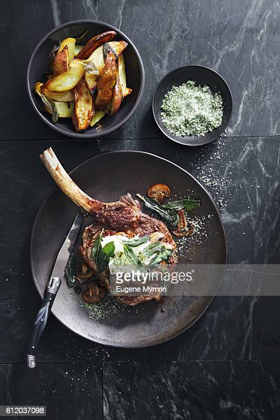 Tomahawk beef steak with mushrooms, burrata and sage potato wedges