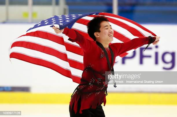Tomaki Hiwatashi of the USA carries the United States flag around the ice after finishing second in the junior mens free skating program during the...