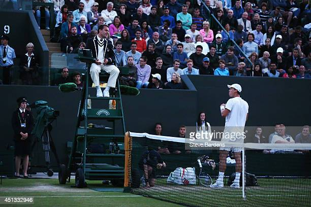 Tomas Berdych of Czech Republic complains to the umpire about how dark it is during his Gentlemen's Singles third round match against Marin Cilic of...