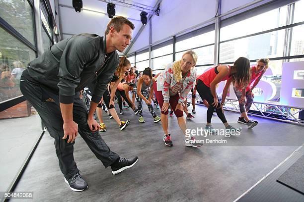 Tomas Berdych of the Czech Republic, Caroline Wozniacki of Denmark, Ana Ivanovic of Serbia and Andrea Petkovic of Germany stretch during the adidas...